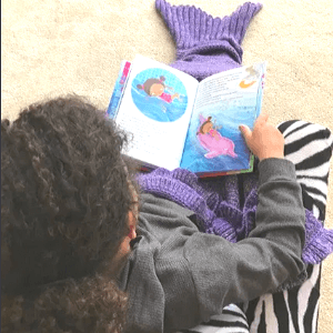 Girl with curly hair reading TimTimTom's Underwater Adventure dressed in a knitted mermaid tail