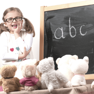 Girl teaches her teddy bears the ABC in German with a chalkboard