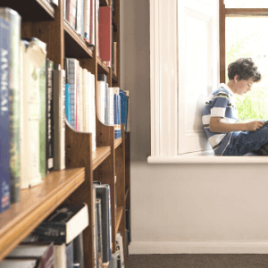 Boy sitting on a window sill of a library reading a book in French
